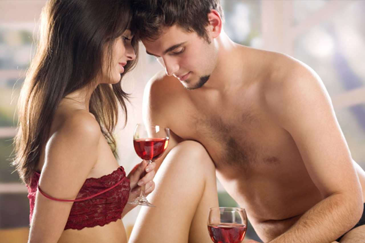 Couple having wine on bed