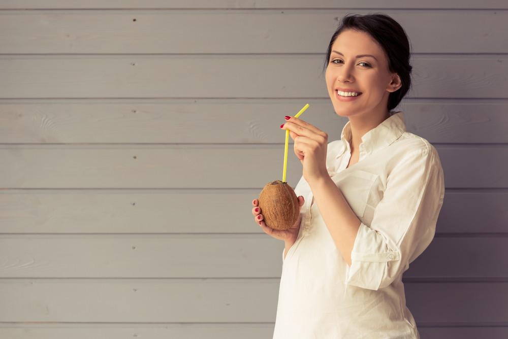 Pregnant woman drinking coconut milk